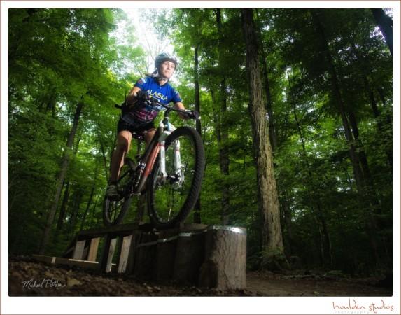 Female mountain bike rider on an elevated skinny platform